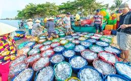 Mui Ne, Wietnam, Kwiecień 23, 2018: Targowa wczesna wioska rybacka gdy ludzie ruchliwie kupienia sprzedawania ryba, transport ryb zdjęcie stock