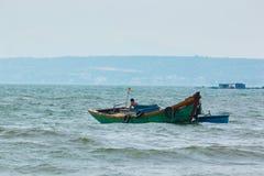 MUI NE, WIETNAM - 02 11 2017: Rybak w łodzi na plaży przy wioski rybackiej Mui Ne, Wietnam Zdjęcie Royalty Free