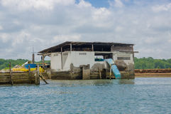 Muisne,厄瓜多尔- 2016年3月16日:小水泥工厂厂房坐与连接入的蓝色管子的河岸 图库摄影