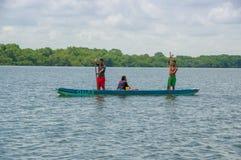 Muisne,厄瓜多尔- 2016年3月16日:站立里面绿色独木舟的两个人,当坐下另外一个的人,时 图库摄影