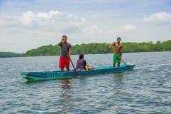 Muisne,厄瓜多尔- 2016年3月16日:站立里面绿色独木舟的两个人,当坐下另外一个的人,时 免版税库存图片