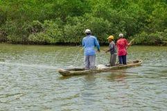 Muisne,厄瓜多尔- 2016年3月16日:钓鱼使用接近岸的网的三个人从有绿色的木传统独木舟 免版税库存图片