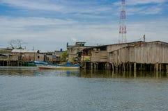 Muisne,厄瓜多尔- 2016年3月16日:Muisne江边回家如被看见从水,谦虚水泥房子坐杆 免版税库存照片