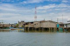 Muisne,厄瓜多尔- 2016年3月16日:Muisne江边回家如被看见从水,谦虚水泥房子坐杆 免版税库存图片