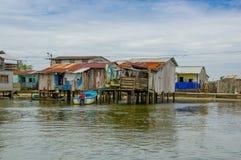 Muisne,厄瓜多尔- 2016年3月16日:Muisne镇如被看见从水,谦虚木房子坐杆江边 库存照片