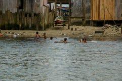 Muisne, эквадор - 16-ое марта 2016: Очень загрязнянный пляж городка Muisne, местные дети плавая и наслаждаясь вода Стоковая Фотография