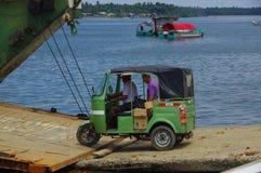 Muisne, эквадор - 16-ое марта 2016: Паром зеленого традиционного корабля транспорта tuktuk входя в от пристани Muisne Стоковые Фото