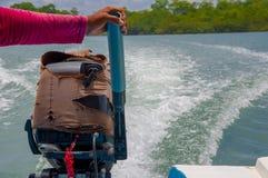 Muisne, эквадор - 16-ое марта 2016: Удерживание руки на двигатель шлюпки, трассировку волны видимую на воде от управлять, большой Стоковые Фотографии RF