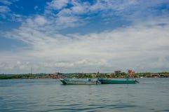 Muisne, Ecuador - 16 de marzo de 2016: Barcos de pesca tradicionales atados juntos en el mar, la ciudad en fondo y el azul hermos Fotografía de archivo
