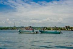 Muisne, Ecuador - 16 de marzo de 2016: Barcos de pesca tradicionales atados juntos en el mar, la ciudad en fondo y el azul hermos Foto de archivo libre de regalías