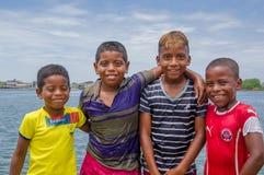 Muisne, Ecuador - 16 de marzo de 2016: Niños locales adorables que presentan feliz para la cámara que se abraza con el Océano Pac Imagen de archivo libre de regalías