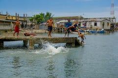 Muisne, Ecuador - 16 de marzo de 2016: Niños locales y adolescentes que juegan feliz el salto del embarcadero en el océano, prese Imagenes de archivo