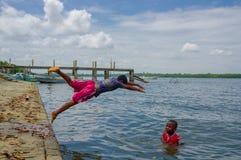 Muisne, Ecuador - 16 de marzo de 2016: Niños que se zambullen y que nadan en el Océano Pacífico de la superficie de piedra con ro Fotografía de archivo libre de regalías