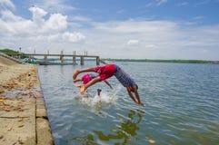 Muisne, Ecuador - 16 de marzo de 2016: Niños que se zambullen y que nadan en el Océano Pacífico de la superficie de piedra con ro Fotografía de archivo