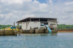 Muisne, Ecuador - 16 de marzo de 2016: Pequeño edificio industrial concreto que se sienta en riverbank con el tubo azul que conec Fotografía de archivo