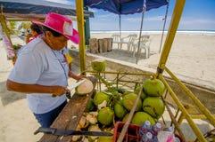 Muisne, Ecuador - 16. März 2016: Lokale Straßenhändlerfunktion und mit Messer auf grünen Kokosnüssen, strandnaher Pazifischer Oze Lizenzfreie Stockbilder