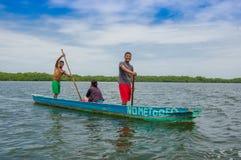 Muisne, Ecuador - 16. März 2016: Zwei Leute, die inneres grünes Kanu während eine weitere Person sich hinsetzt, heraus an stehen Stockfotos