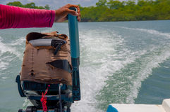 Muisne, Ecuador - March 16, 2016: Arm holding onto boat engine, wave trace visible on water from driving, great Royalty Free Stock Photos