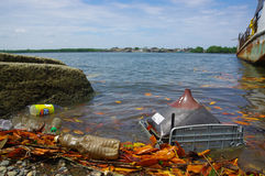 Muisne, Ecuador - March 16, 2016: Different trash floating in the water next to ferry pier Stock Photos