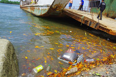 Muisne, Ecuador - March 16, 2016: Different trash floating in the water next to ferry pier Royalty Free Stock Images