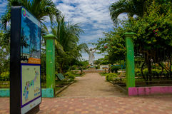 Muisne, Ecuador - March 16, 2016: Entrance to local park with statue of Jesus inside, green trees and red stone surface Royalty Free Stock Photo