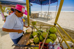 Muisne, Ecuador - March 16, 2016: Local street vendor working and using knife on green coconuts, beachside pacific ocean Royalty Free Stock Images