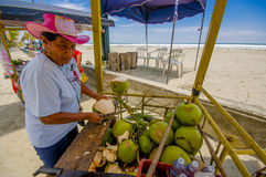 Muisne, Ecuador - March 16, 2016: Local street vendor working and using knife on green coconuts, beachside pacific ocean Stock Photos