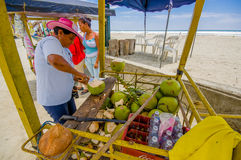 Muisne, Ecuador - March 16, 2016: Local street vendor working and using knife on green coconuts, beachside pacific ocean Stock Photo