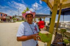 Muisne Ecuador - mars 16, 2016: Lokal gatuförsäljare som lyckligt poserar med den gröna kokosnöten, beachside Stilla havet Arkivbild