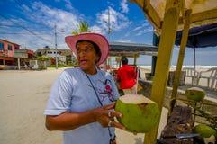 Muisne Ecuador - mars 16, 2016: Lokal gatuförsäljare som lyckligt poserar med den gröna kokosnöten, beachside Stilla havet Royaltyfria Bilder