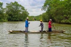 Muisne Ecuador - mars 16, 2016: Tre grabbar som fiskar genom att använda netto nästan kusten från den trätraditionella kanoten me Royaltyfri Foto