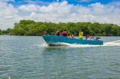 Muisne, Ecuador - 16 marzo 2016: Gruppo di persone, gli adulti ed i bambini dentro fishingboat blu tipico che guida di fianco Fotografia Stock Libera da Diritti