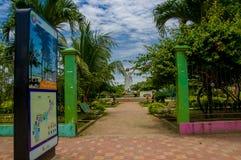 Muisne, Ecuador - 16 marzo 2016: L'entrata al parco locale con la statua di Gesù dentro, gli alberi verdi e la pietra rossa sorgo Fotografia Stock Libera da Diritti