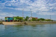 Muisne, Ecuador - 16 marzo 2016: La parte della città come veduta dall'acqua, mura di cemento incontra l'oceano con verde blu di  Immagine Stock