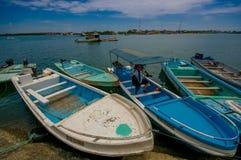 Muisne, Ecuador - 16 marzo 2016: Parecchi fishingboats tipici hanno parcheggiato al pilastro locale con il fondo dell'oceano Paci Fotografia Stock Libera da Diritti