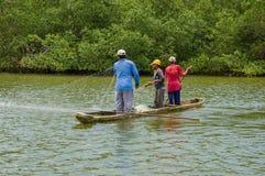 Muisne, Ecuador - 16 marzo 2016: Tre tipi che pescano facendo uso della rete vicino alla riva dalla canoa tradizionale di legno c Fotografia Stock Libera da Diritti