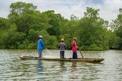 Muisne, Ecuador - 16 marzo 2016: Tre tipi che pescano facendo uso della rete vicino alla riva dalla canoa tradizionale di legno c Fotografie Stock Libere da Diritti