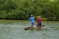 Muisne, Ecuador - 16 marzo 2016: Tre tipi che pescano facendo uso della rete vicino alla riva dalla canoa tradizionale di legno c Fotografia Stock