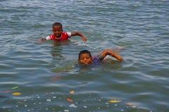 Muisne Ekwador, Marzec, - 16, 2016: Dzieciaki pływa w pokojowym oceanie od kamienia ukazują się z odziewają dalej Zdjęcia Stock