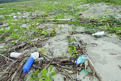 MUISNE, EKWADOR MAY 06, 2017: Plażowy zanieczyszczenie z garvage wewnątrz i grat na plażowej powoduje szkodzie środowisko Fotografia Stock