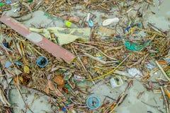 MUISNE, EKWADOR MAY 06, 2017: Plażowy zanieczyszczenie z garvage wewnątrz i grat na plażowej powoduje szkodzie środowisko Zdjęcie Stock