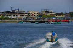 Muisne, Equateur - 16 mars 2016 : Équipez l'eau typique de croisement de bateau de pêche d'intérieur de position de Muisne au con Image stock