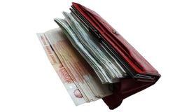 Muita mentira do dinheiro do russo em uma bolsa de couro vermelha em um fundo branco Fotografia de Stock