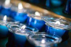 Muita vela azul da cera no vidro Close-up Luz da vela em um frasco de vidro reto imagens de stock royalty free