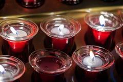 Muita vela vermelha da cera no vidro Close-up Luz da vela em um frasco de vidro reto Fotos de Stock