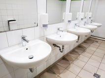 Muitas bacias de lavagem com os espelhos na parede em um toalete público fotografia de stock royalty free