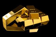 Muitas barras de ouro brilhantes no preto fotos de stock royalty free