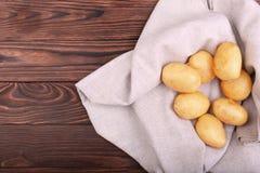 Muitas batatas cruas e novas em uma luz - saco cinzento e em um fundo de madeira do marrom escuro Batatas novas cruas, limpas, fr Imagens de Stock
