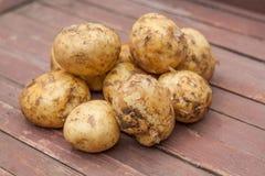 Muitas batatas em uma bacia na tabela de madeira fotografia de stock royalty free
