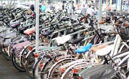 Muitas bicicletas estacionadas, povos borrados Fotos de Stock